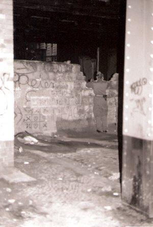 DDR Soldat schaut über die Mauer