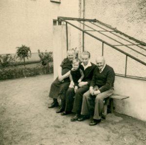 Familie auf der Bank vor dem Haus